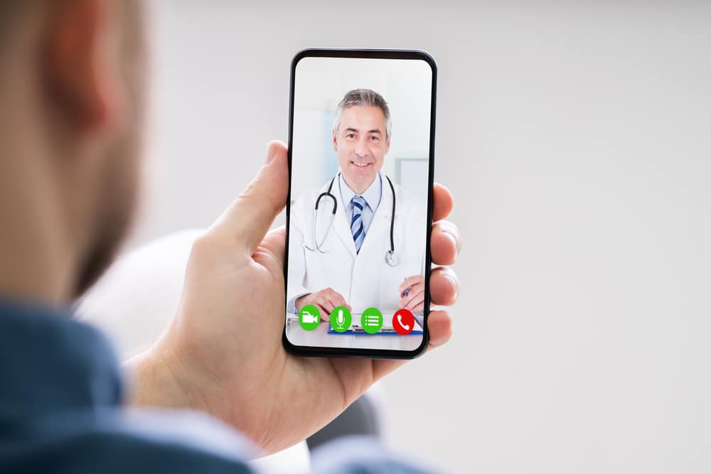 Close-up of a video call on a phone with a doctor