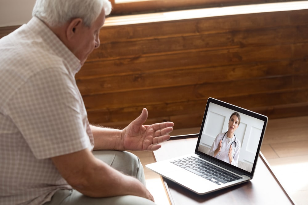 A man speaking with a doctor through a computer