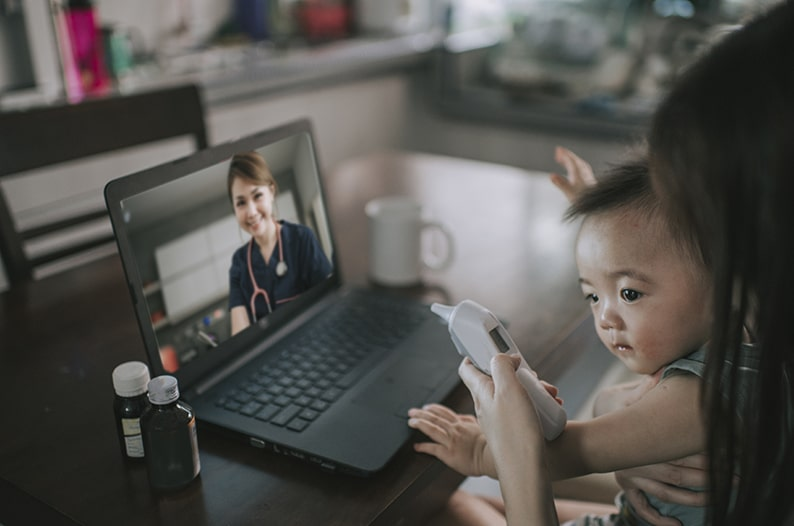 Parent with her child speaking to a doctor through a computer